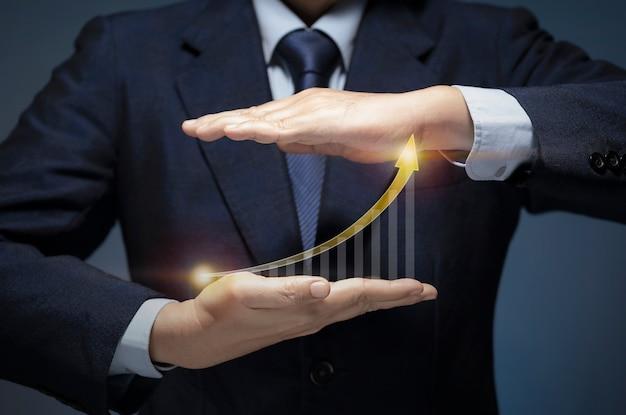 ビジネスマンは、矢印グラフでビジネスプランを提示し、高い成長率を示します。ビジネスマンは、ビジネスの成功、財務、販売利益、株式市場への投資、経済成長の概念を示す利益チャートを表示します。
