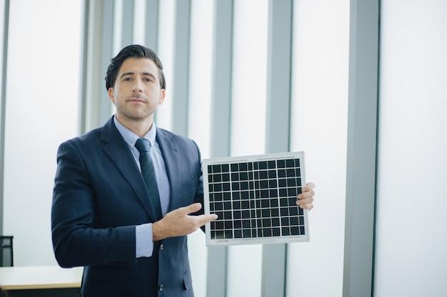 Деловой человек представляет концепцию окружающей среды солнечной энергии