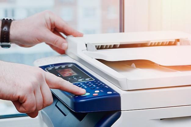 Деловой человек, нажав кнопку панели принтера, чтобы сделать копию документа в офисе