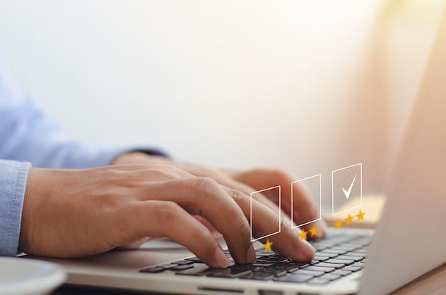 ノートパソコンのノートパソコンのキーボードの顧客サービス評価の概念に絵文字を押すビジネスマン顧客の世話をする