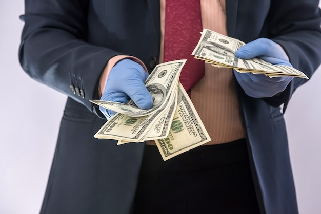 Business man in protective gloves with money isolated on white background. medical concept covid 19 coronavirus