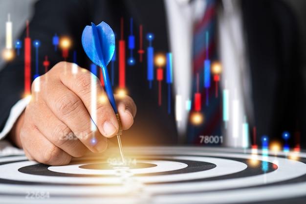 ビジネスマンはダーツボード、株式市場、金融の概念にターゲットを置きます