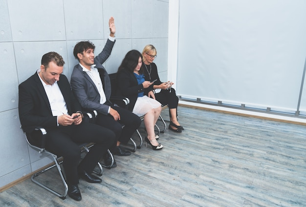 Business man raise his hand ready for job interview while other business people using smartphone