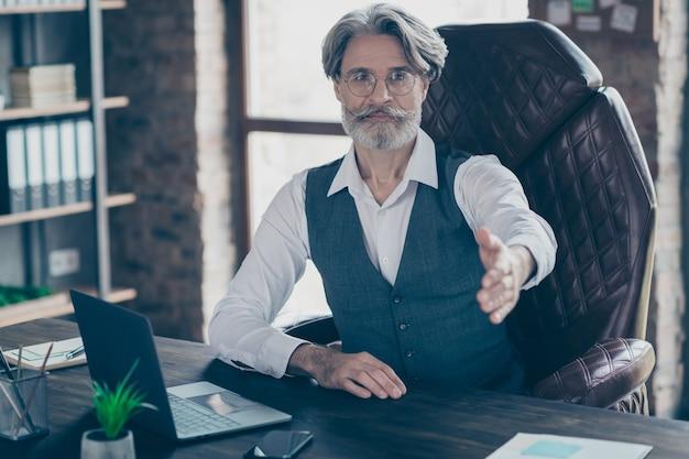 ワークステーションオフィスで握手のために手を上げるビジネスマン