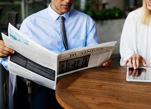 Business man reading newspaper and business woman using a tablet
