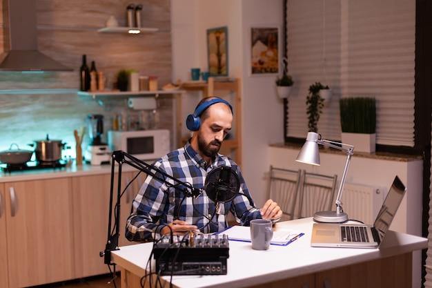 テーブルの上にラップトップを持ってホームスタジオでトークショーを録音するビジネスマン。 reative online showオンエアプロダクションインターネット放送ホストストリーミングライブコンテンツ、デジタルソーシャルメディアコミュニケーションの記録