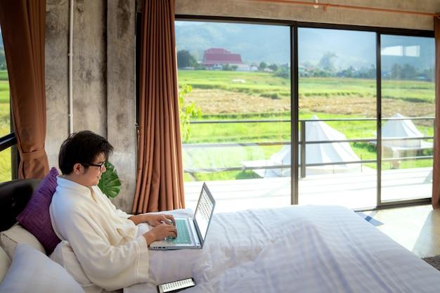 ビジネスの男性がリラックスして、ベッドルームのコンピューターでの作業