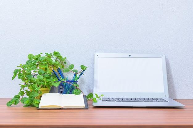 Портативный компьютер делового человека находится за столом