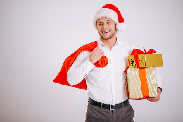Business man in santa hat holding christmas present isolated