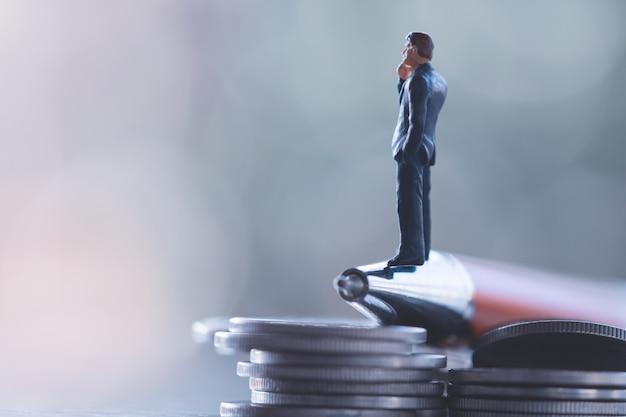 ビジネスの男性、節約、投資と金融の概念。ミニチュア人スタンド