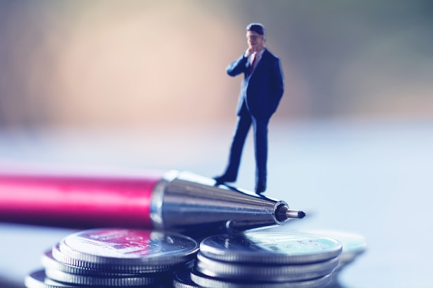Business man,saving,investment and finance concepts. miniature people stand