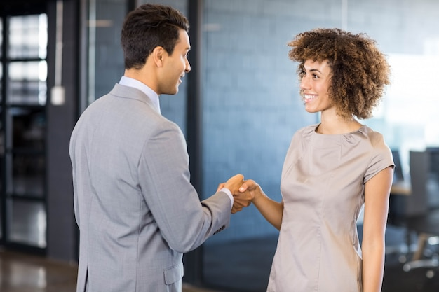 Business man shaking hands young woman in office