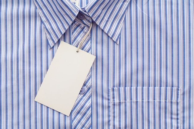 Business man shirt form or formal blue shirt in a checked blue pattern with blank white label or tag attached