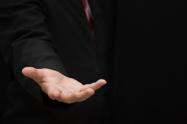 黒のシャツを着て空の手を示すビジネスマン