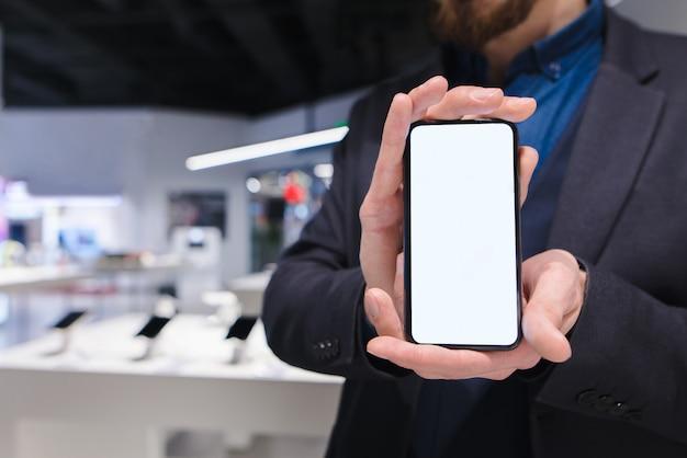 ビジネスの男性は、電気店を背景にトレンディなスマートフォンを示しています。