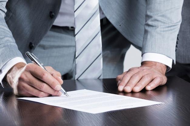 テーブルの近くに立っているビジネスマンの署名契約