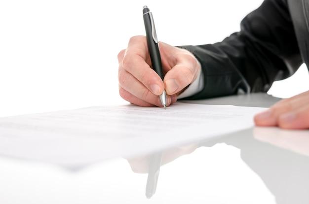 Деловой человек подписывает контракт на белом столе. с избирательной направленностью.