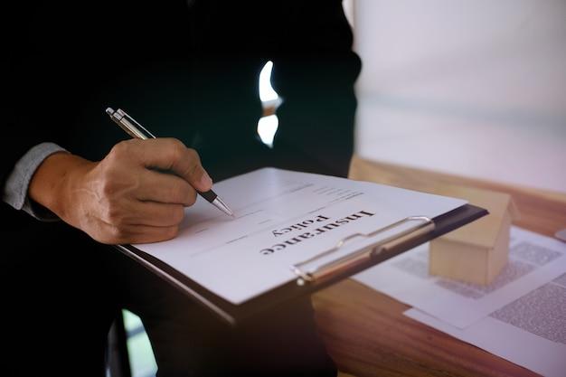 不動産業者と契約を結ぶビジネスマンサイン契約コンサルタントと家保険の概念の概念。