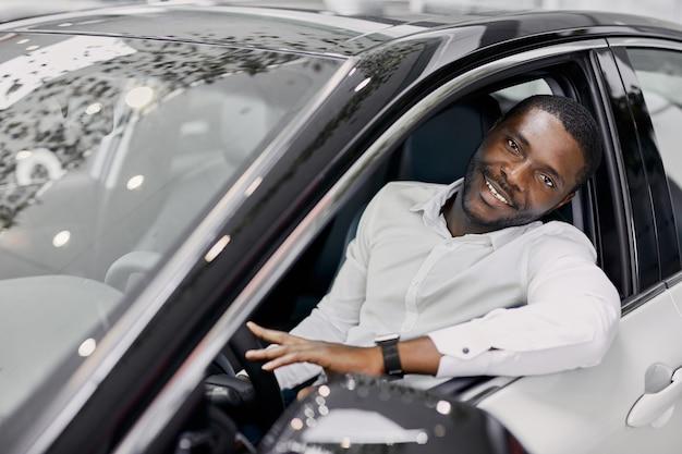 ビジネスマンはディーラーで高価な高級車の中に座っています