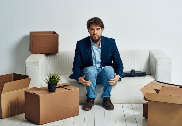 비즈니스 남자는 전문적인 물건을 포장 노트북 상자 근처 소파에 앉아