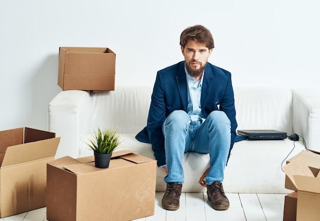 ビジネスマンは、荷物を詰めてラップトップボックスの近くのソファに座っています