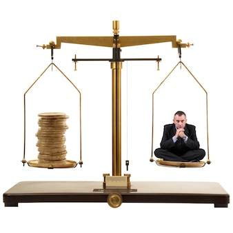 Business man sittin on old gold scale with coins stack isolated on white background