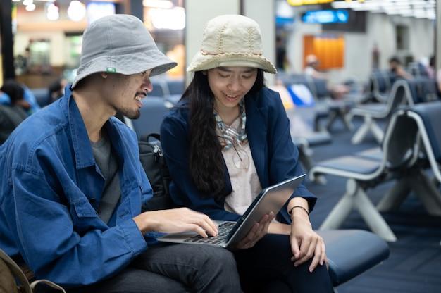 공항에서 일하기 위해 노트북 컴퓨터를 사용하여 앉아 있는 사업가, 젊은 사람들은 여행을 가거나 공항 출발 시 실내에서 기다릴 때 업무를 위해 인터넷 통신 기술을 가지고 있습니다.
