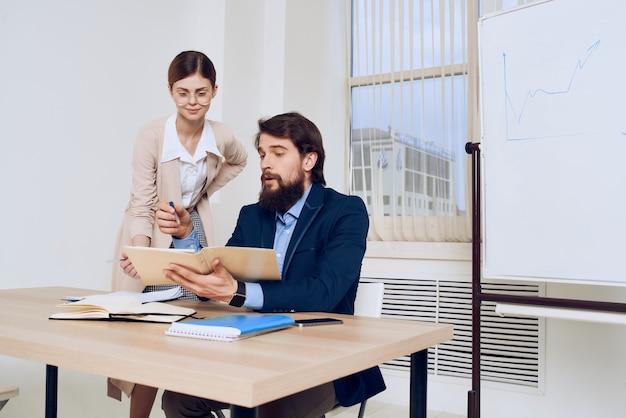 秘書のコミュニケーションの仕事の隣に彼の机に座っているビジネスマン