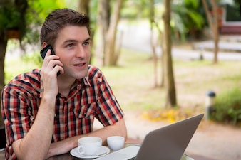 Business man sitting at table in cafe using mobile phone and lap