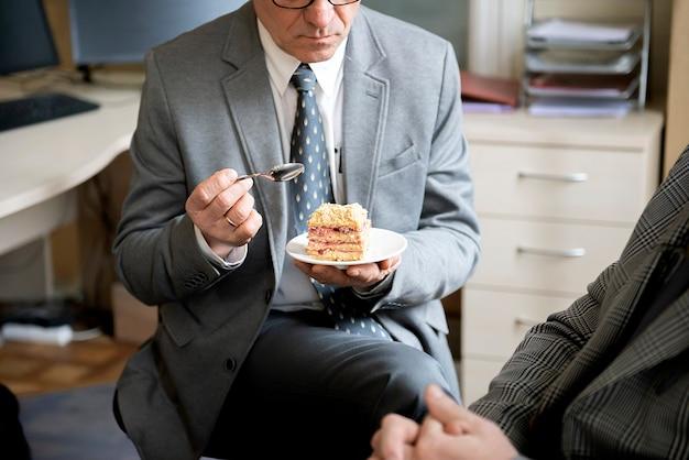 Деловой человек сидит за столом и ест медовый торт, перерыв на кофе в офисе
