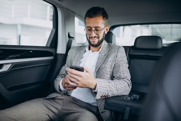 Business man sitting on the back sit of a car using tablet