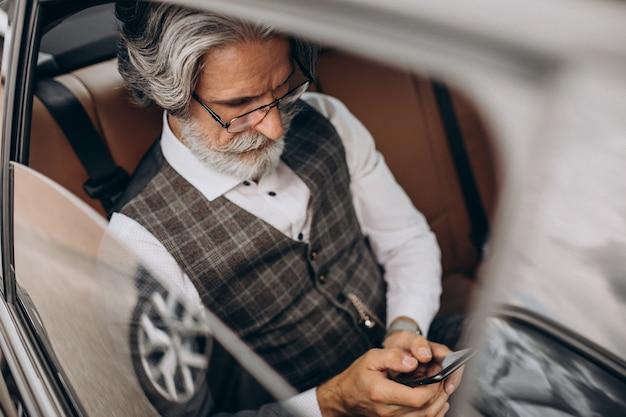 L'uomo d'affari seduto nella sua macchina sul retro si siede