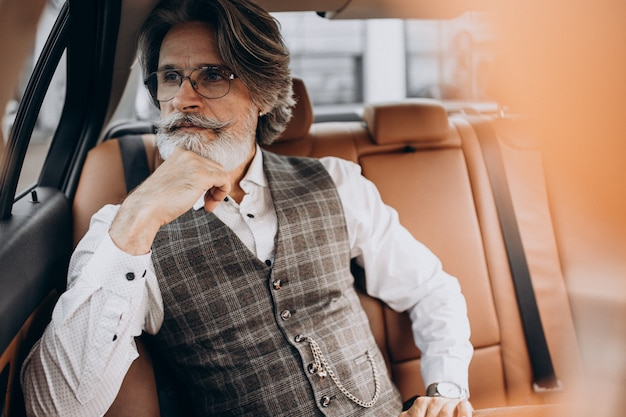 後ろに座って彼の車に座っているビジネスマン