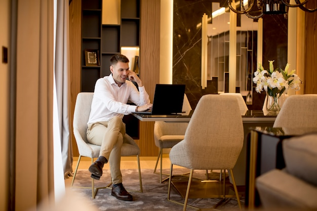 Business man sitting in a luxurious room in front of a laptop