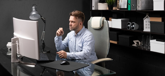 Business man sitting in office at computer desk and holding his mouth shackle of glasses