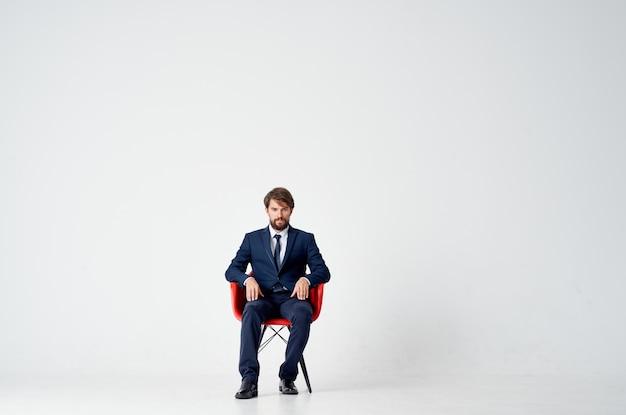 Деловой человек, сидящий на красном стуле, работает в офисе менеджера
