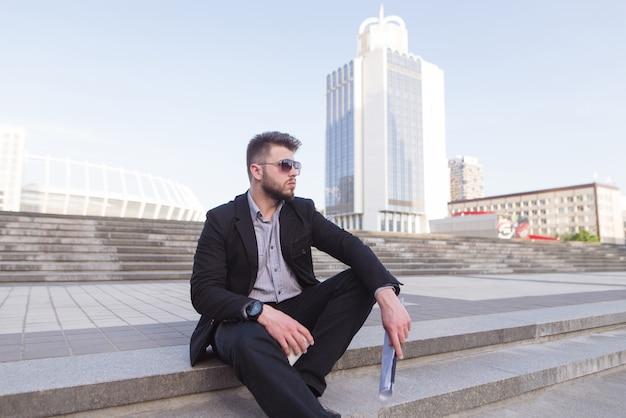 Бизнесмен сидя на лестницах на фоне современной архитектуры.