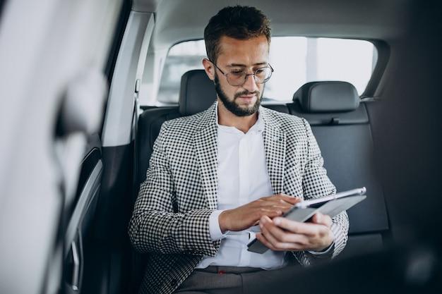 Деловой человек сидит на заднем сиденье автомобиля с помощью планшета
