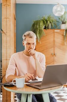 Деловой человек сидит с ноутбуком и смартфоном. бизнесмен в кафе работает и проверяет компьютер