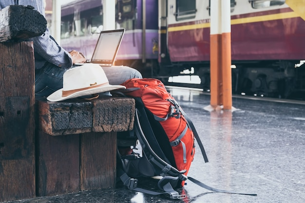 노트북을 사용 하여 앉아 사업가입니다. 기차역에서 여행 가방. 빈티지 필터 효과. 측면보기.