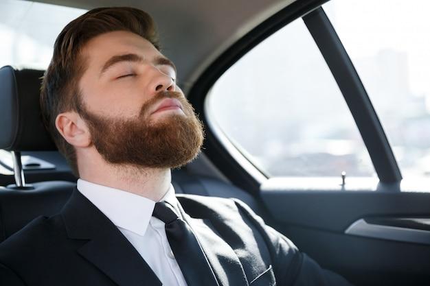 車の後部座席で寝ているビジネスマン