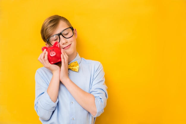 Business man. smiling teenage boy holding a red piggy bank. business concept. saving money concept. bank advertising. piggybank. finance