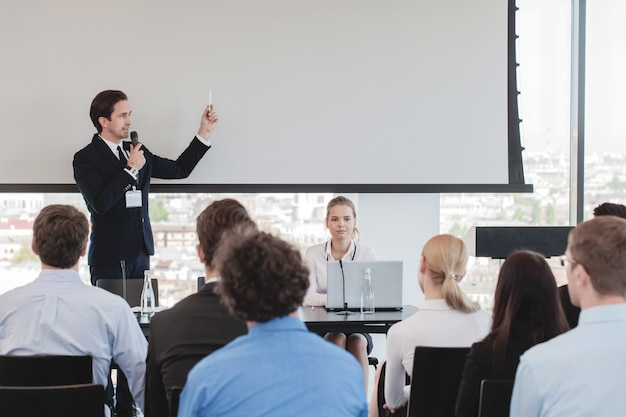 Деловой человек, выступающий на презентации в микрофон в офисе
