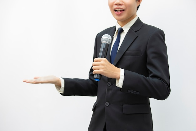 Business man speaking and holding microphone at conference.