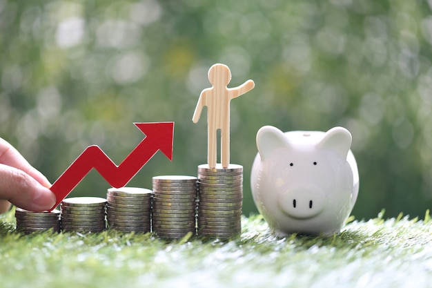 Business man on stack of coins money with hand holding red arrow graph and piggy bank on natural green background