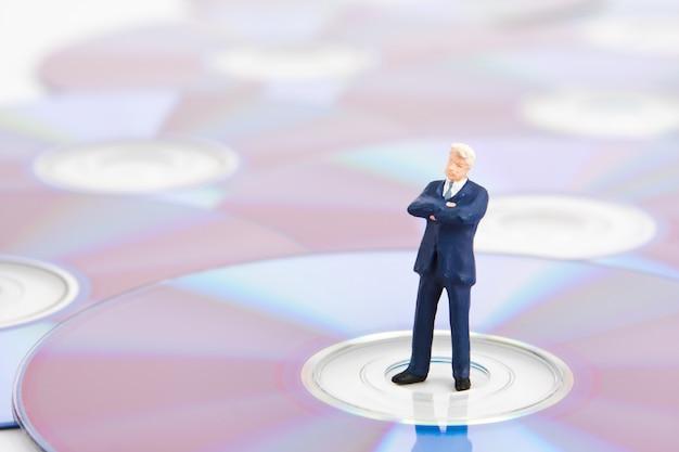 Business man standing on computer cds