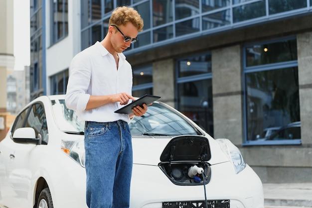 전기 자동차를 충전하고 거리에서 태블릿을 사용하는 비즈니스 남자.