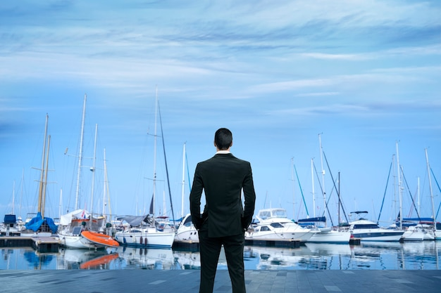 Business man standing at yacht club