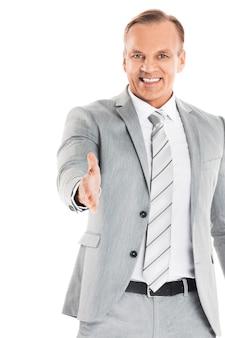 Деловой человек протягивает руку для тряски и улыбки, изолирован на белой стене