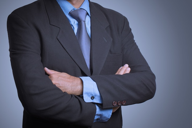Business man in a stylish suit standing with folded arms